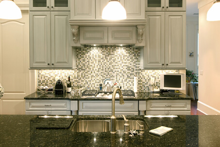 Glass Mosaic Tiled Backsplash in a White Kitchen with Raised Panel Cupboards