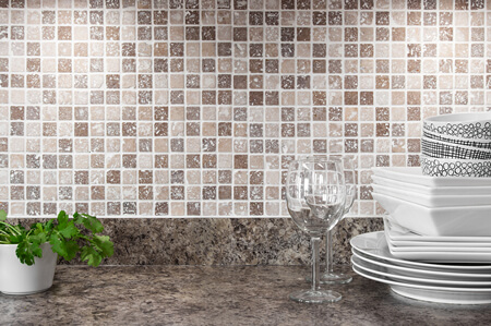 Mosaic Backsplash and Granite Counter with Wine Glasses and Dishes