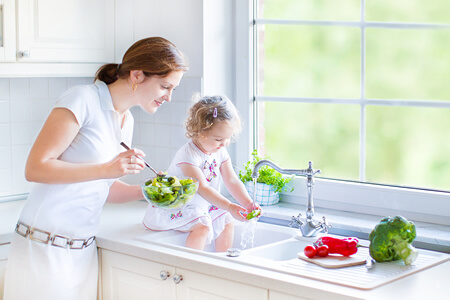 A Mother and Child Washing Vegetables in Kitchen Sink