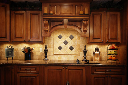 Tuscan Kitchen with Embellished Backsplash and Exhaust Hood Over Cook Area